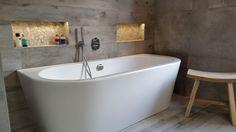 Badkamer gerealiseerd door Sanidrome Scharenborg uit Haaksbergen. Het halfvrijstaande bad geeft een goed ruimtelijk effect, met daarboven 2 verlichte nissen voor de nodige sfeer.