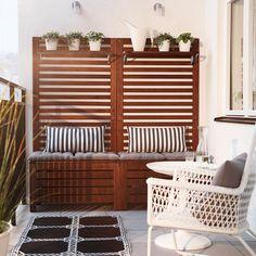 Terraza con bancos de madera marrones con cojines de asiento, paneles de pared y estantes con plantas verdes