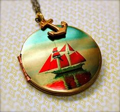 A vintage locket 1960s opens to hold two good sized photographs, pressed flowers, secrets...    It has been given a screen print of a dreamy sailboat