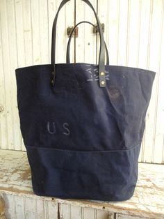 VINTAGE US MILITARY TOTE - Heavy duty, extra large tote made from WWII era, air-force navy blue canvas with original print. The lining is heavy duck canvas and the straps are 8/9oz thick leather with about a 6.5 drop. The bag measures a very generous 22 (at the widest point) x 16 x 11 deep. This is a great size for a weekend or travel bag and can seriously hold a ton of stuff!  ** All bags are made with great care in selection of materials and craftsmanship. All seams are double sewn and…