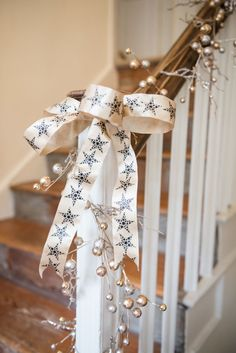 CHRISTMAS DECORATIONS THEME: SPARKLE & SHINE. Simply swathe a V V Rouleaux gold berry pear garland around your bannister and attach a gold metallic star ribbon bow and your Christmas staircase is complete.