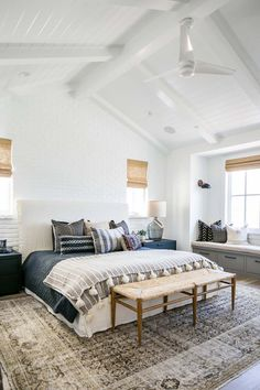 A white ceiling fan is mounted to a vaulted white plank ceiling above a rush seat bench placed on a gray overdyed rug in front of a white slipcovered bed complemented with dark blue bedding accented w Boho Chic Interior, Bohemian Bedroom Design, Boho Chic Bedroom, Blue Bedroom, Home Interior, Master Bedroom, Blue Bedding, Bedroom Inspo, Bedroom Designs