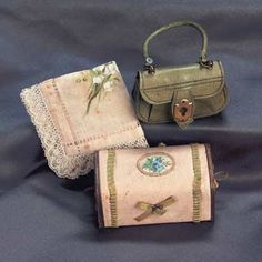 Exquisite French doll accessories for poupées or small bébés, circa 1875, including kidskin purse in rare moss green color, a dainty hankie with lace edging and hand-painted designs of lily of the valley, and a valise- shaped candy box with silk ribbon and decoupage trim, with slide-box interior.