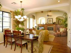 An open archway connects this warm, tropical dining room to the adjacent living room. The pattern in the dining room chairs is carried through to the window treatments to create a unified look.