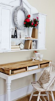 Wood pallet table top desk with a white frame & legs. White distressed cabinet/shelf, & an ivory distressed chair with a throw pillow to add comfort. The wreath, red flowers in a vase, clock, books & other trinkets provide a complete look.