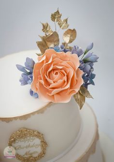 Handmade gum paste peach-coloured roses, gold leaves and lilac freesias.