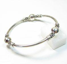 Ce bijou indien est un bracelet jonc en argent 925. Il a trois boules et des motifs travaillés. C'est un bijou argent classique qui se porte seul ou avec d'autres bracelets argent.