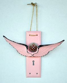 A wall hanging I made with an old door plate and ceramic wings :)