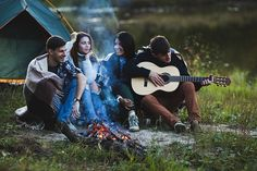 Man playing guitar while sitting with friends at bonfire