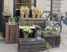 The wooden crates used in this florist front are a great idea for floral displays; along with the karts and old fashioned bikes