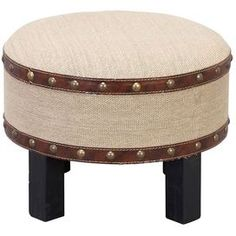 """Bring worldly appeal and chic sophistication to your home with this stylish design. Product: OttomanConstruction Material: Wood, burlap and leatheretteColor: Brown and beigeFeatures:   Richly texturedLeatherette trimNailhead detailingDimensions: 12"""" H x 16"""" Diameter"""