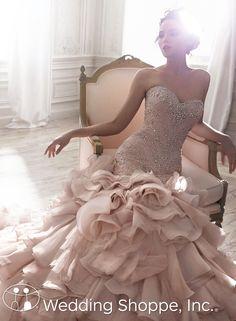 Romantic blush wedding dress with dramatic skirt.
