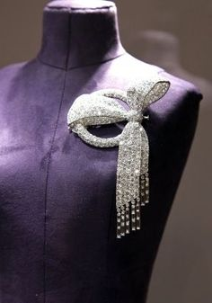 A Van Cleef & Arpels art deco diamond bow brooch is on display during a press preview of Elizabeth Taylor's