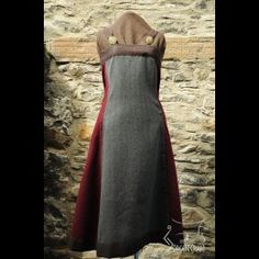 From the Jorgencraft site.  A decorated Viking apron dress based on Haithabu finds, 10th cent. Made of grey (herringbone pattern) and maroon wool.  Upper and lower edges are bordered with brown linen. The straps are made up of loops, through which the brooch pins are threaded and closed. Broches are not included. Size: length of apron dress 98 cm (without shoulder), upper width measured on flat fabric 93 cm, lower width measured on flat fabric 186 cm.
