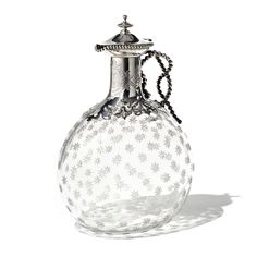 A Silver-mounted Claret Jug by Robert Hennell, of bulbous form, the clear glass container etched with eight pointed stars to the surface. Mounted in silver, with a pierced fretwork collar, the handle formed from a beaded rope design, with further beading to the finial & pourer. The neck of the jug is decorated with an elaborate cartouche,   within which is written 'VR to JB, Christmas 1872'. Maker's mark: 'RH'  London, 1860 (inscription later). From http://www.wartski.com/ Archive/Silver