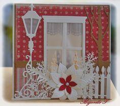 """Carte """"façade de maison"""" dont le lampadaire, la branche de sapin, le poinsettia et les bougies sont des dies de Marianne Design. Les vitres en papier calque laissent filtrer la lumière si l'on met une bougie LED derrière."""