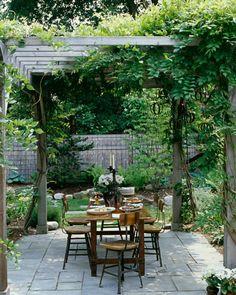 lugar bajo la pérgola para comer en el jardín