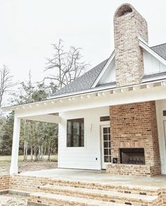 Dream House Outdoor fireplace - white farmhouse - black windows - exposed rafters on porch (not sure what it's called) Modern Farmhouse Exterior, Rustic Farmhouse, Farmhouse Style, Farmhouse Fireplace, Double Fireplace, Porch Fireplace, Fireplace Ideas, Farmhouse Design, Fireplace Stone