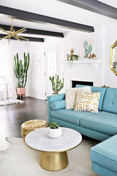 Midcentury modern living room with black ceiling beams, a gold chandelier, cacti, and a blue sectional