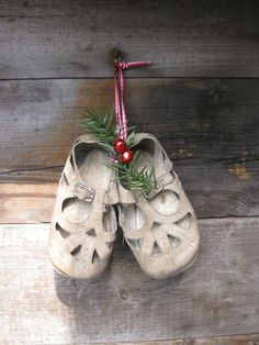 ANTIQUE BABY SHOES HUNG FROM RIBBON WITH GREENERY.