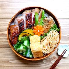 Grilled honey chicken bento box, featuring pasta, tamagoyaki, pickled cucumbers, fried kabocha squash slices, boiled asparagus, white rice, and a carrot flower.
