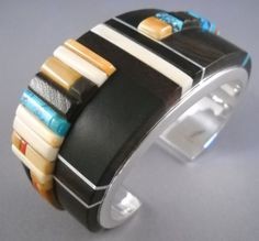Cuff | Verma Nequatewa. Sterling silver with inlays of ebony, fossilized ivory and turquoise. She takes much inspiration from the work of her uncle, Charles Loloma