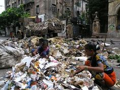 India Slums: Dalits digging through trash to find food, clothes, or items for their home.