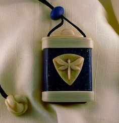 Polymer Clay Inro by Randee Ketzel. Polymer clay inro in faux lapis lazuli and ivory, dragonfly ornament on cover.