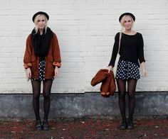 navy shorts with white polka dots black sweater black tights black shoes brown jacket