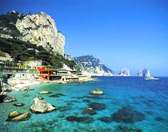 Capri, Italy, Europe: A gaily-colored Capri village, with the Faraglioni as backdrop