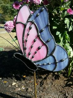 Butterfly created in stained glass. Use for garden decoration or inside plants The butterfly was created using 2 different glasses, the first is a light pink solid, the other is a light purple. The body is black glass. Hand formed wire antenna, decorative solder on wire wing details.