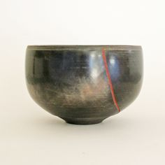 """Petrus Spronk. Bowl Small bowl broken and reassembled, with burnished and finely hatched surface, mainly coal black but ecru on one of the joined surface some bowls have a spiral on the base.  Petrus Spronk was born in Holland and emigrated to Australia in 1957 """" He makes bowls of primal power, black in colour, burnished to look like coal, sometimes broken and reassembled, and decorated with gold in the manner of an icon."""""""