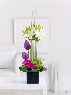 Lily and Anthurium Arrangement. This elegant and striking gift features the very finest fresh Asiatic lilies above a bed of sumptuous colour. It is a real design statement, resulting in a breath-taking centrepiece.