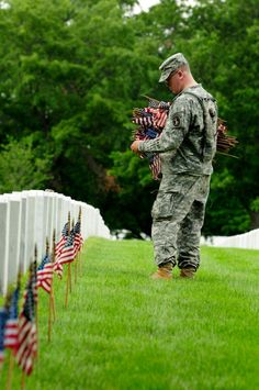A 3d U.S. Infantry Regiment (The Old Guard) Soldier places an American flag in front of fallen veteran's grave stone at Arlington National Cemetery. Each year for the past 40 years, the 3d U.S. Infantry Regiment has honored America's fallen heroes by placing American flags at gravestones just prior to Memorial Day weekend. (Photo by Sgt. Jose Torres) - MilitaryAvenue.com