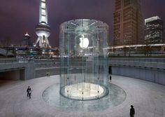 The cylindrical glass entrance into the Shanghai Apple store is innovative as there is nothing else like it, a standout in its surroundings you can see the stair case that leads down to the store lit up by the Apple logo.