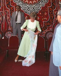 13 May 1992: Princess Diana removes her shoes and prepares to cover her hair appropriately with a floral silk scarf before touring Al Azhar Mosque in Cairo, Egypt