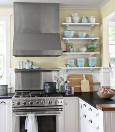 Open shelving shows off this homeowner's colorful ceramics collection.     #kitchens #decorating