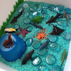 Hudson's Ocean Sensory Tub - blue rice (8 cups rice, 8T rubbing alcohol with 1 oval blue watercolor solid dissolved in the alcohol. Place all in ziplock, shake & layout on lined baking pan to dry for 4+ hours), blue glass pebbles, sushi grass and small ocean animals.