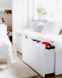 Nahaufnahme von STUVA Banktruhen in Weiß/Weiß mit Schaffell und Kissen darauf.