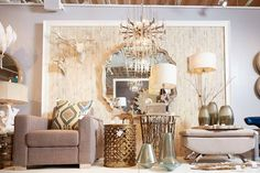 Winter themed displays and vignettes mirrors, side tables, mirrors, wall art, and lighting, featuring warm metal tones, various blues, vibrant golden glass