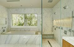 This beautiful bathroom features marble floors and walls and a large double shower situated next to a large soaking tub with outside views. 612 E. Channel Road | Santa Monica
