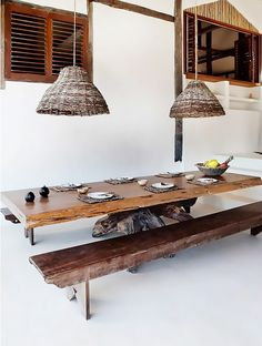Rustic dining space with whitewashed walls, a reclaimed wood table, and wicker pendant lights