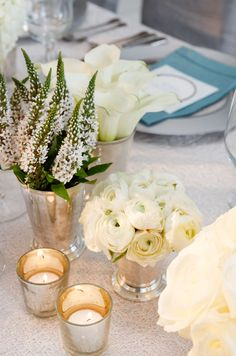 Mono floral arrangements of ranunculus, calla lilies and white veronica look luxe in silver vases of varying heights.