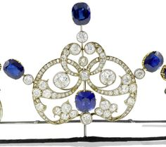 A belle époque sapphire and diamond tiara, circa 1905  Composed of three highly stylised meandering foliate motifs, the central cartouche set to the centre with a cushion-shaped sapphire, within an openwork border of old brilliant and rose-cut diamonds, surmounted by three cushion-shaped sapphires, between two similarly set scrolls, each scroll motif detachable from frame, central cartouche may be converted to a brooch