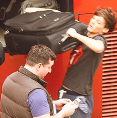 louis working on his biceps, while paul is texting
