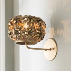"""This Young House Love metal daisies wall sconce blooms in a gold metallic wash painted finish. This cheerful sconce light will brighten any room. 40 watt max. medium base lamp.(9""""Hx8""""Wx12""""D)5"""" round backplate, can be installed up or down."""