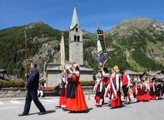 """Gressoney-Saint-Jean - Festa di San Giovanni - I festeggiamenti cominciano la sera del 23 giugno: in tutte le frazioni si accendono falò e festeggiano con brindisi e """"spisie"""" (tipici spuntini). Il 24, giorno del Patrono, si celebra la Messa seguita dalla processione: le donne sfilano in costume  Walser, i ragazzi sostengono una portantina con la testa decapitata di San Giovanni, i coscritti portano la statua ed un uomo robusto la """"grande croce"""". Viene poi impartita una benedizione ai bambini"""