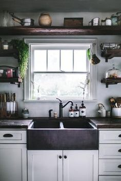 dark farmhouse sink and exposed plank open shelf