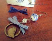 Orecchino anticato nichelfree con perla di ceramica con fiori blu, perla, fiocco azzurro, uccellino bronzo.  Lunghezza complessiva: 6,5cm.