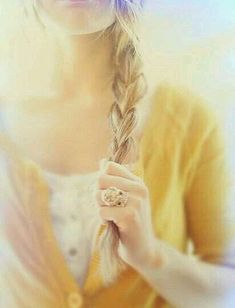 Woman with a long blond braid who is wearing a yellow sweater poses.